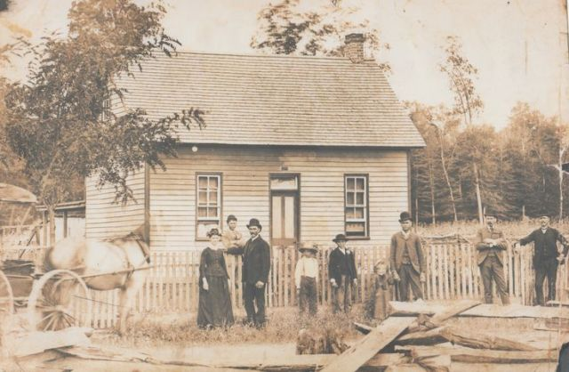 John Homestead 1892 on the west side of S Co Road 600S.  LtoR Caroline, Lawrence, John, Alex, Albert, Mary holding William's hand, George, and Henry at the far right.
